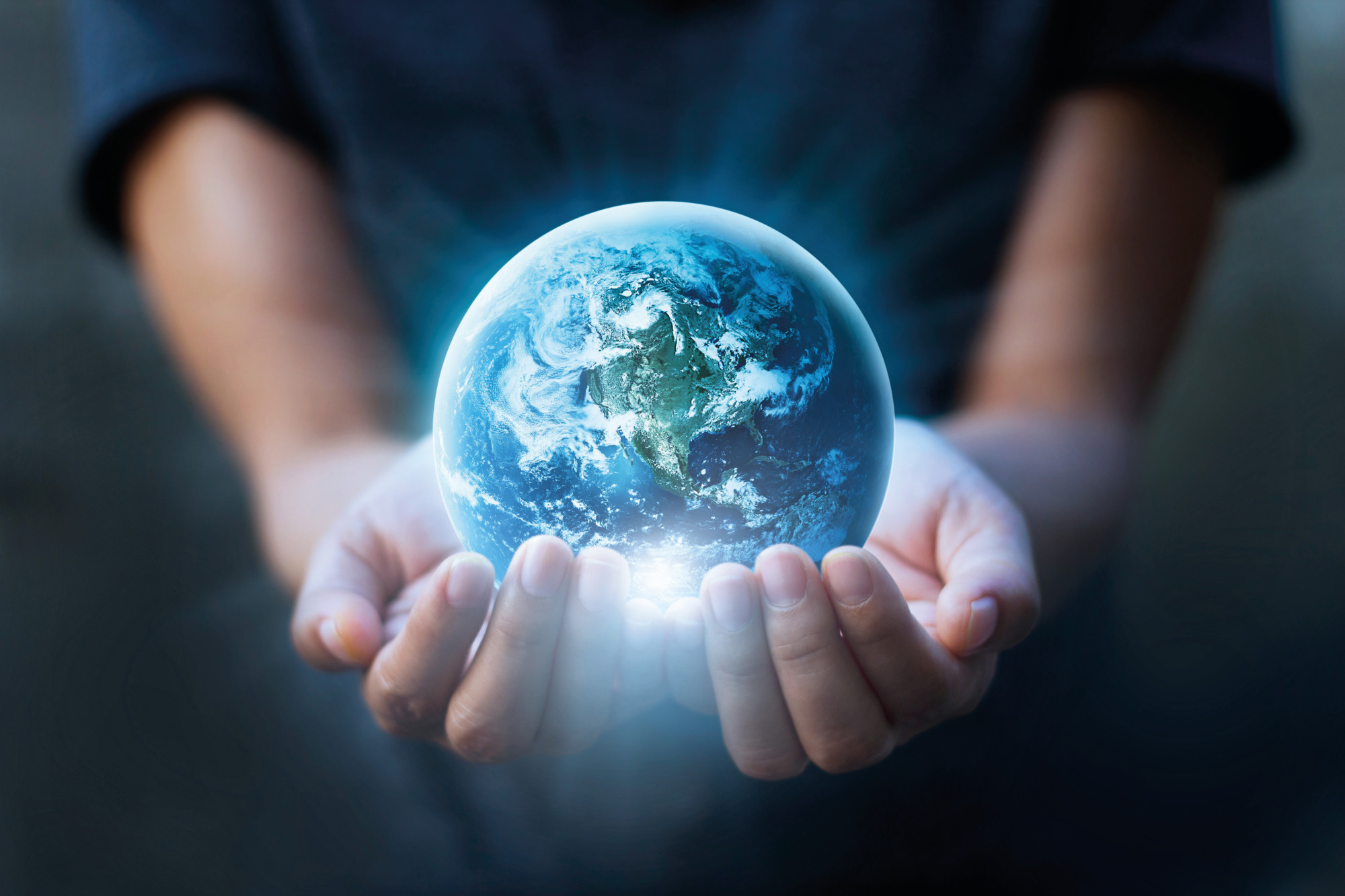 Human hands holding blue earth